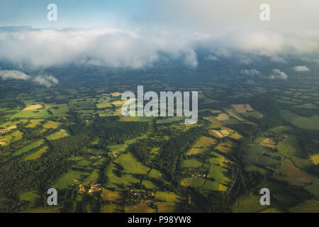 patches of grassy green British farmland seen while flying into the United Kingdom - Stock Photo