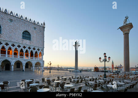 Saint Mark square with empty sidewalk tables, nobody at sunrise in Venice, Italy - Stock Photo