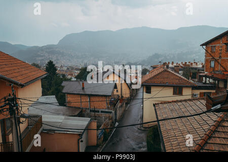 Looking out through the narrow streets of a hillside suburb in Sarajevo, one rainy afternoon - Stock Photo
