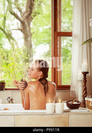 Pretty woman in the bathroom with an open window to the garden, enjoying peaceful day on the spa resort, beauty and health treatment - Stock Photo