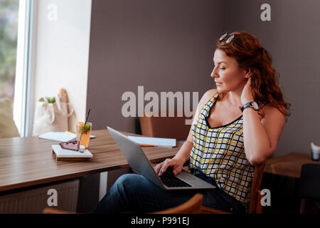 Remote worker having lunch break in cafe - Stock Photo