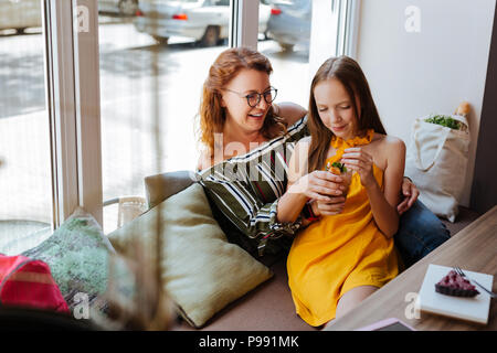 Beautiful teenage girl leaning on her happy mother - Stock Photo