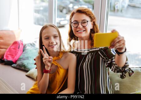 Modern loving mother making selfie with teenage daughter - Stock Photo