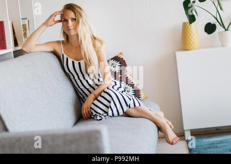 Image of young woman sitting on gray sofa - Stock Photo