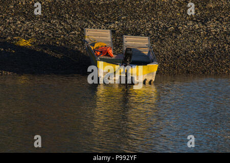 Dingy with the evening glow on the water - Stock Photo