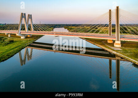 New modern double cable-stayed bridge over Vistula River in Krakow, Poland, and its reflection in water. Part of the ring motorway around Krakow under - Stock Photo