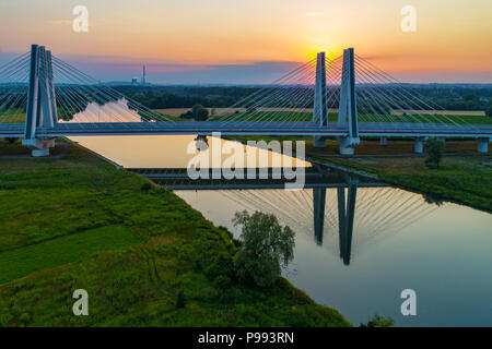 New modern double cable-stayed bridge over Vistula River in Krakow, Poland and its reflection in water at sunset. Part of the ring road around Krakow. - Stock Photo