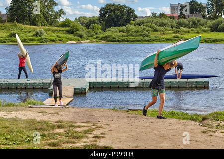 Polotsk, Belarus - July 6, 2018: Young man and girls lifted canoe on their backs and carried them for storage after training in rowing. - Stock Photo