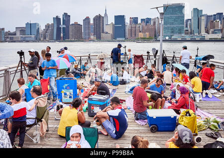 New York City, USA - July 4, 2018: People wait to watch Fourth of July Independence Day fireworks at a Long Island pier. - Stock Photo
