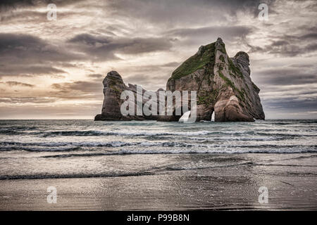 The Archway Islands off Wharariki Beach at the northern tip of New Zealand's South Island. - Stock Photo
