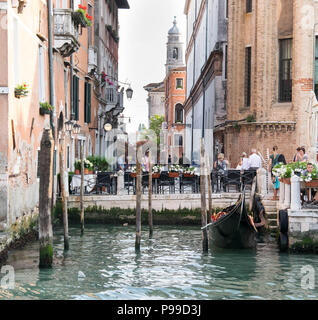 Europe, Italy, Veneto, Venice. People sitting at the restaurant near Ponte del Accademia, Gallerie dell Accademia, at the Grand Canal in Venice. - Stock Photo
