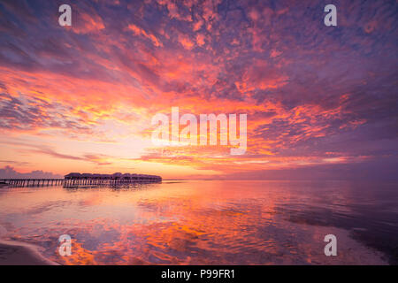 Sunset on Maldives island, luxury water villas resort and wooden pier. Beautiful sky and clouds and beach background for summer vacation holiday - Stock Photo