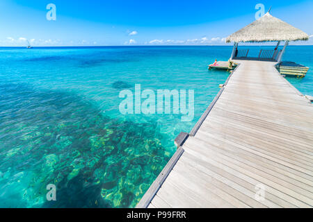 Luxury over water bungalows in tropical sea under blue sky. Tranquil vacation background - Stock Photo