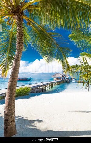 Maldives island, luxury water villas resort and wooden pier. Beautiful sky and clouds and beach background for summer vacation holiday and travel - Stock Photo