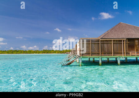 Luxury over water bungalow and villas side view with beautiful blue sea and lagoon - Stock Photo