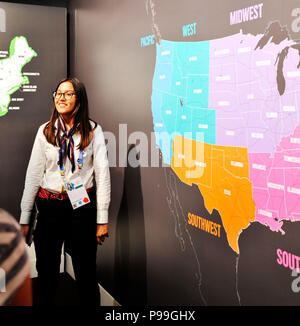 Milan, Italy – July 30 2015: Woman of oriental origin shows the map of the United States of America. Real photo taken during the EXPO 2015 in Milan, I - Stock Photo