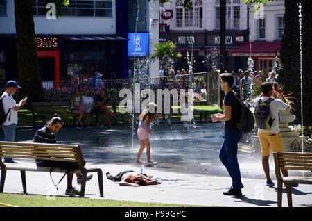 a homeless woman passed out in leicester square gardens london with tourists 2018 - Stock Photo