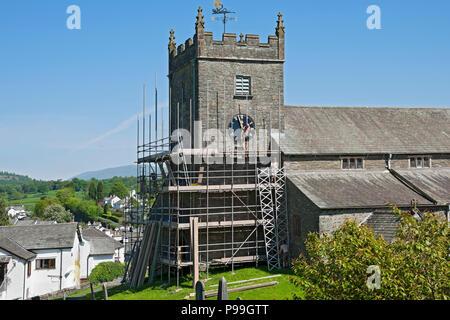 Men erecting scaffolding on village church Hawkshead Cumbria England UK United Kingdom GB Great Britain - Stock Photo