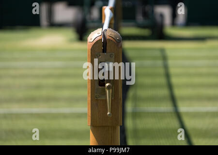 Close up of net and mechanism, and well manicured grass tennis court at Wimbledon, photographed during the 2018 championships. - Stock Photo