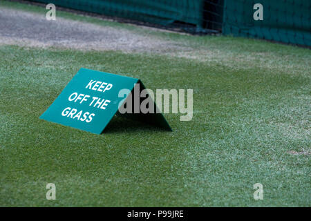 Close up of tennis court at Wimbledon, with sign saying 'keep off the grass' photographed during the 2018 championships. - Stock Photo