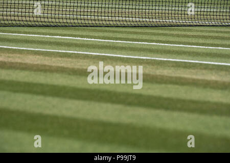 Close up of well manicured grass tennis court with net in the background  at Wimbledon, photographed during the 2018 championships. - Stock Photo