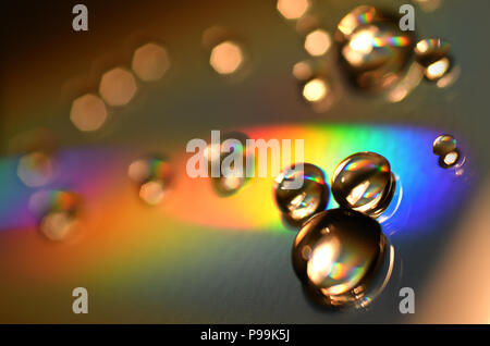 Water Drops on CD and DVD. Colorful background. - Stock Photo