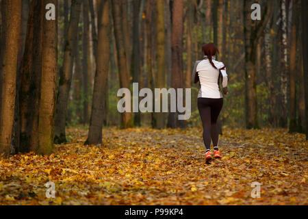 Picture from back of young sports girl in running through forest - Stock Photo