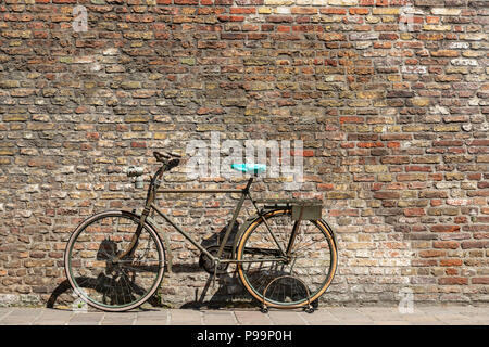 Old styled bike abandoned against an old brick wall, back streets, Bruges, Belgium - Stock Photo