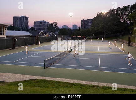 A group of people playing tennis outside at dusk in Oakville, Ontario, Canada. - Stock Photo
