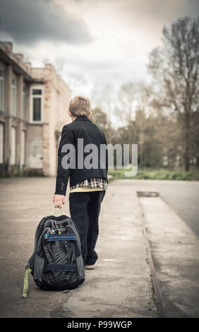 The boy wearily goes to school and drags on the ground a school backpack - Stock Photo