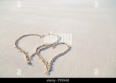 Two hearts drawn in white sand on tropical beach scene - Stock Photo