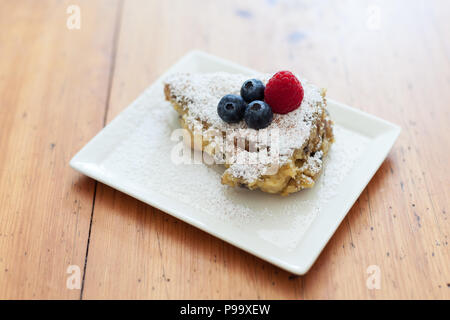Kaiserschmarren with powdered sugar and berries on a plate on a wooden table - Stock Photo