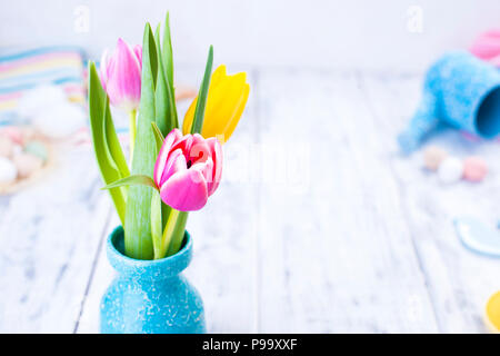 A bouquet of spring tulips of pink and yellow in a vase on the table. White background. Free space for text or a postcard. Easter. - Stock Photo