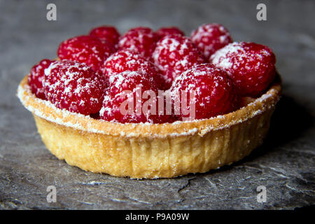 Raspberry tart made with shortcrust pastry dusted with icing sugar presented on a Cornish slate surface. - Stock Photo