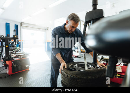 Mature man working in tire service workshop. Mechanic removing tire from wheel on machine. - Stock Photo