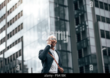 Smiling businessman talking over cell phone while commuting to office with a glass facade building in background. Man in formal clothes carrying offic - Stock Photo