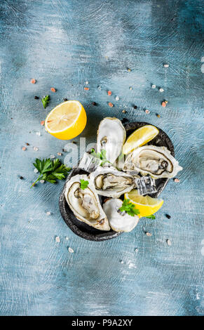 Fresh raw seafood, oysters with lemon and ice on a light blue background - Stock Photo