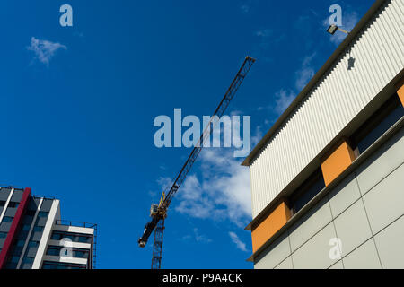 Construction crane against the background of new houses and blue sky - Stock Photo