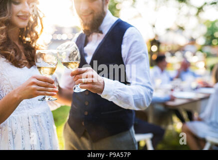 Bride and groom clinking glasses at wedding reception outside in the backyard. - Stock Photo