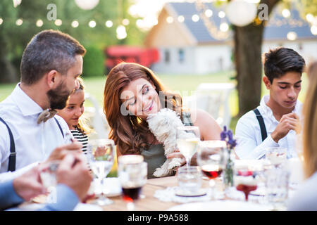 Guests with a small dog sitting at the table outside in the backyard. - Stock Photo