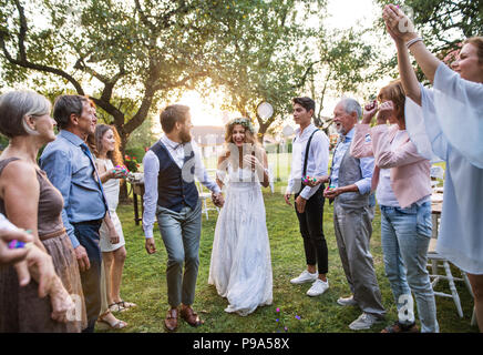 Bride, groom and guests at wedding reception outside in the backyard. - Stock Photo