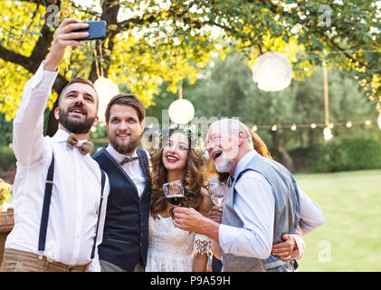 Bride, groom and guests with smartphone taking selfie outside at wedding reception. - Stock Photo