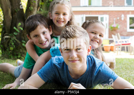 Portrait Of Four Brothers And Sisters Lying In Garden At Home - Stock Photo