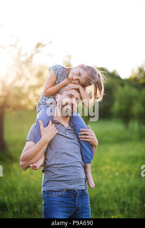 Father giving small daughter a piggyback ride in spring nature. - Stock Photo