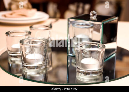 candles in glasses standing on a table - Stock Photo
