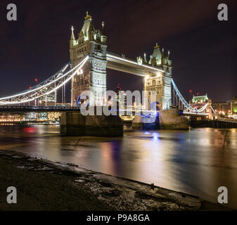 View of Tower Bridge lit up at night from the banks of the River Thames, London, with the Gherkin in the distance