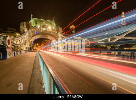 Long exposure showing light trails from cars and buses travelling over Tower Bridge, London, at night with the Shard lit up in the distance - Stock Photo