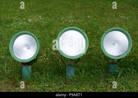 Three small spotlights on a green lawn in the Park. - Stock Photo