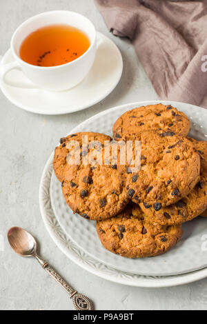 Homemade cookies with chocolate in a plate on a grey table. Chocolate chip cookie shot. - Stock Photo