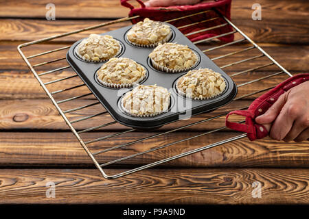Carrot cupcakes with lemon and apple, almonds on wooden background, raw silicone form on a baking sheet - Stock Photo